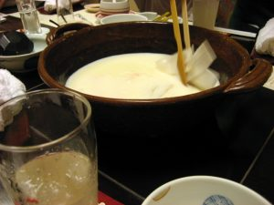 Adding raw vegetables to the heated soy milk at tofu restaurant near Machida Station, Tokyo