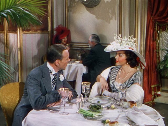Screenshot from Easter Parade. Fred Astaire and Ann Miller in a restaurant scene with celery and pickles on the table.
