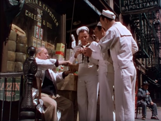 Screenshot from the On The Town film (1949) showing the three main characters sampling cheese in New York's Little Italy