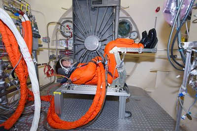 Photo of a person wearing a NASA Pumpkin Suit.  Title of photo is Ambient Pressure Integrated Suit Test (APIST). One PGATA, one ACES (ACES in the seat).  From NASA's Flickr Commons collection